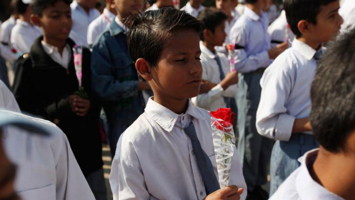 A student holding a rose takes part in a prayer for victims of the Taliban attack on the Army Public School in Peshawar, 17 December 2014 (photo: Reuters/A. Soomro)