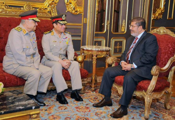 Former Egyptian President, Mohammed Morsi (right), talking to two senior members of the army, including former defence minister and current president, Abdul Fattah al-Sisi (centre) in December 2012 (photo: dpa)