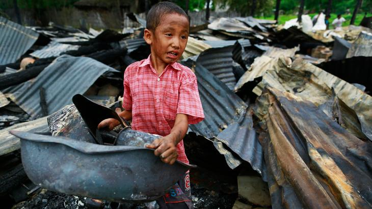 A boy salvages belongings from a burned-down building in Htan Kone village in Myanmar's northern Sagaing region on 25 August 2013 (photo: Reuters)