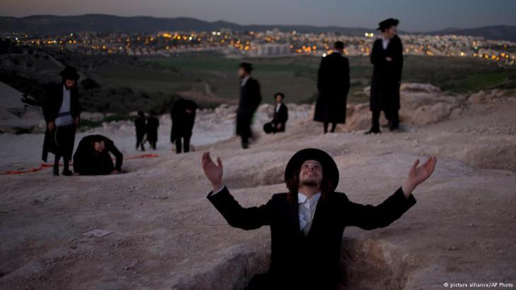 An ultra-Orthodox Jewish man raises his hands during a protest against construction of a new housing project at a site that protesters claim contains ancient graves in Beit Shemesh, Israel, February 2014 (photo: picture-alliance/AP Photo)