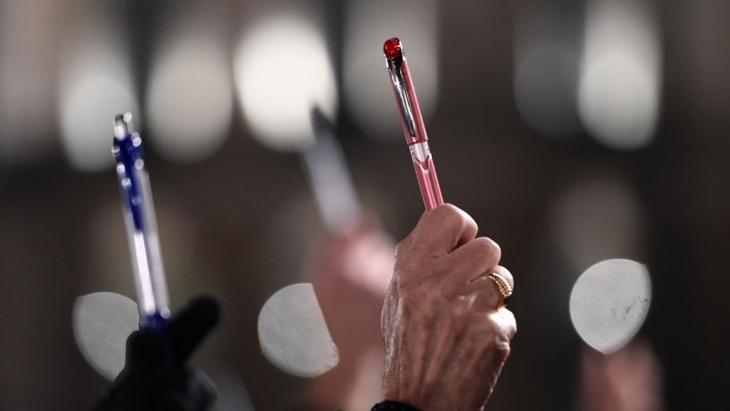 """People in Paris hold up pens in response to the attack on """"Charlie Hebdo"""" (photo: AFP/Getty Images/D. Meyer)"""