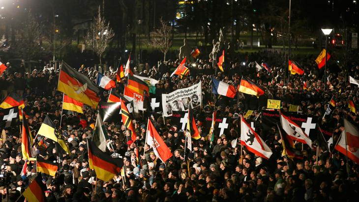 Supporters of the anti-immigration movement Pegida (Patriotic Europeans Against the Islamisation of the West) hold flags during a demonstration in Dresden, 12 January 2015 (photo: Reuters/F.  Bensch)