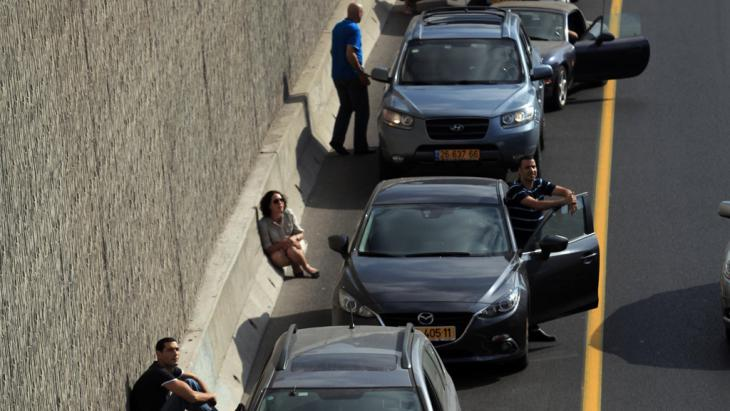 Israelis take cover near their cars while sirens sound over Tel Aviv, 9 July 2014 (photo: picture-alliance//Landov)