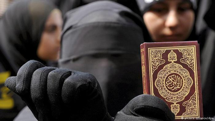 A woman wearing a niqab and holding up a Koran (photo: dpa/picture-alliance)