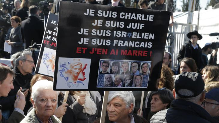 "Mourners at a Jerusalem cemetery on 13 January 2015 attend the funeral of four Jews killed in the attack on a kosher supermarket in Paris the previous week. The French slogans on the placard read: ""I'm Charlie, I'm Jewish, I'm Israeli, I'm French, I'm fed up."" (photo: AFP/Getty Images/J. Guez)"