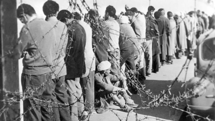 Algerians arrested in Oran in December 1956 stand waiting to be interrogated (photo: dpa/picture-alliance)