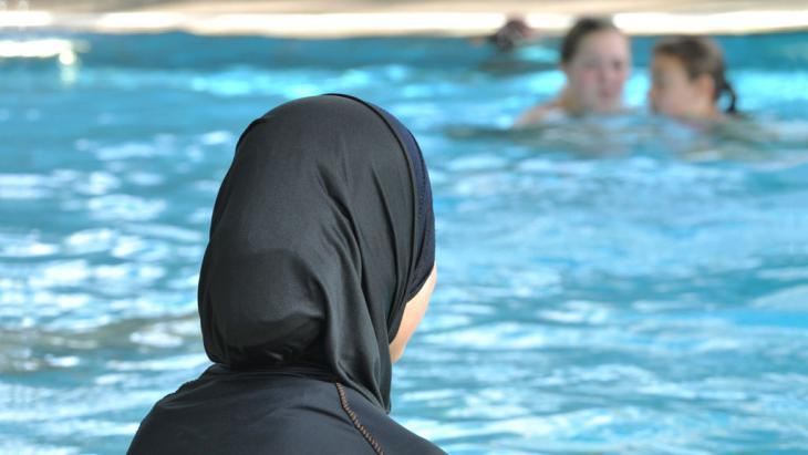 A young Muslim woman in a burkini in a public swimming pool (photo: picture-alliance/dpa/Rolf Haid)