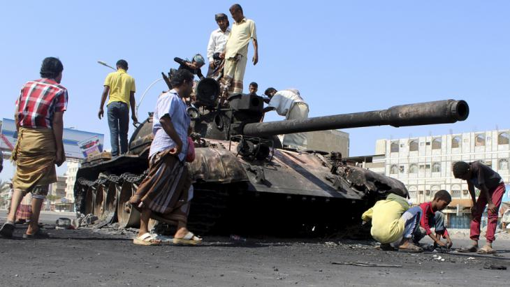 People gather near a tank burnt during clashes on a street in Yemen's southern port city of Aden (photo: Reuters)