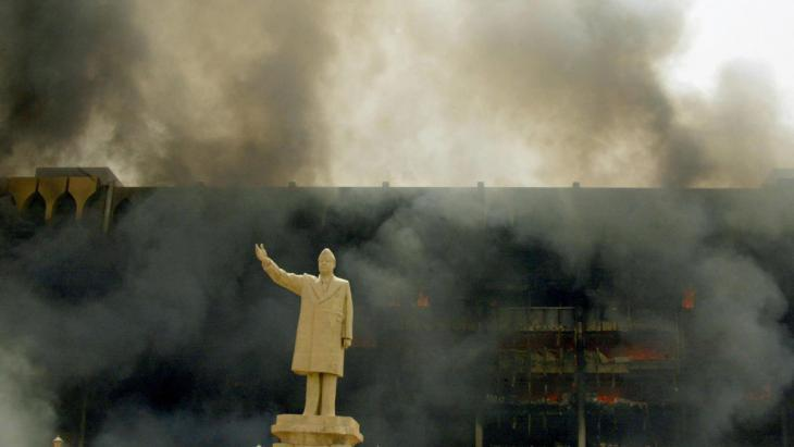 Saddam statue in front of the burning Iraqi Olympic Committee in Baghdad on 9 April 2003 (photo: AFP/picture-alliance)