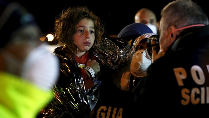 Italian police (right) photograph a child after migrants arrived via boat at the Sicilian harbour of Pozzallo, 19 April 2015 (photo: REUTERS/Alessandro Bianchi)