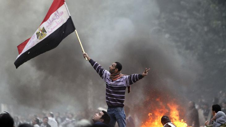 A man waving an Egyptian flag during a riot (photo: AFP/Getty Images/M. Abed)