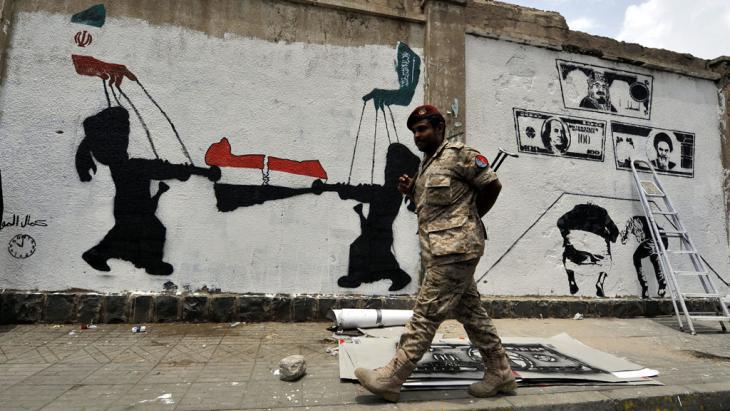 A soldier walks past a wall covered in graffiti indicating the influence of Iran and Saudi Arabia on Yemen (photo: picture-alliance/epa/Y. Arhab)