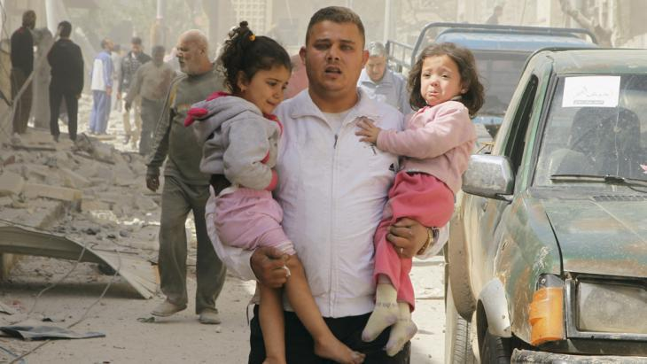 A man carries two children from the ruins of a house in Idlib after a barrel bomb attack orchestrated by the Syrian regime (photo: Reuters/Ammar Abdullah)