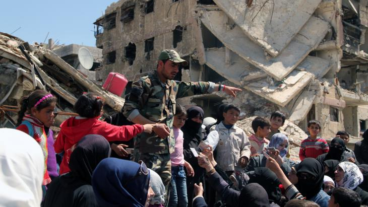 Residents of the Yarmouk refugee camp show their documents to a serviceman in order to leave a dangerous zone (photo: picture-alliance/dpa)