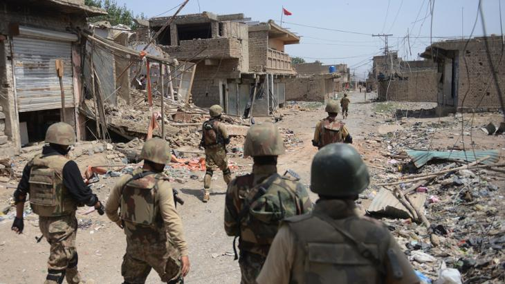 Pakistani soldiers patrol among destroyed houses during a military operation against Taliban militants, Miranshah, North Waziristan, 9 July 2014 (photo: AFP/Getty Images/A. Qureshi)