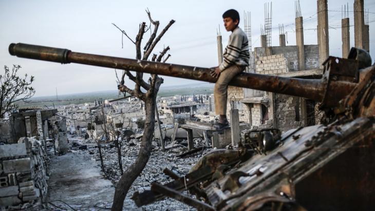 A boy sitting on a tank gun, Ain al-Arab, Syria (photo: Getty Images/AFP/Y. Akgul)