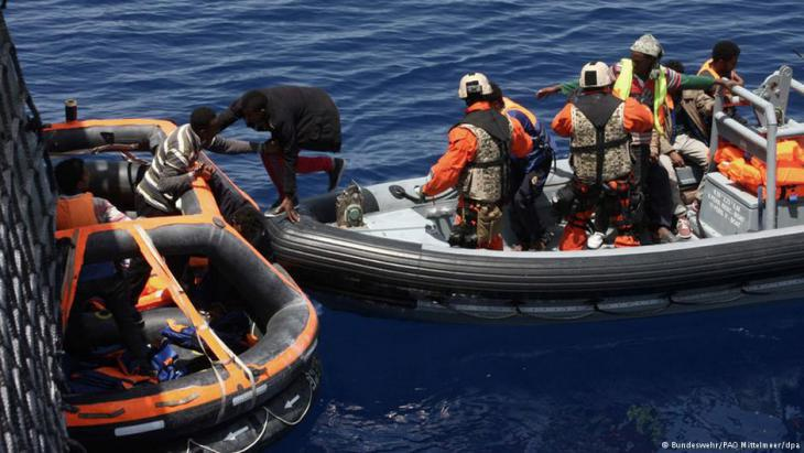 German soldiers pulling refugees from an inflatable boat near Lampedusa (photo: Bundeswehr/PAO Mittelmeer/dpa)