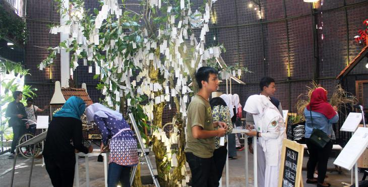 "Visitors at Yoko Ono's ""Wish Tree"" at ""Artjog"" 2015 (photo: Christina Schott)"