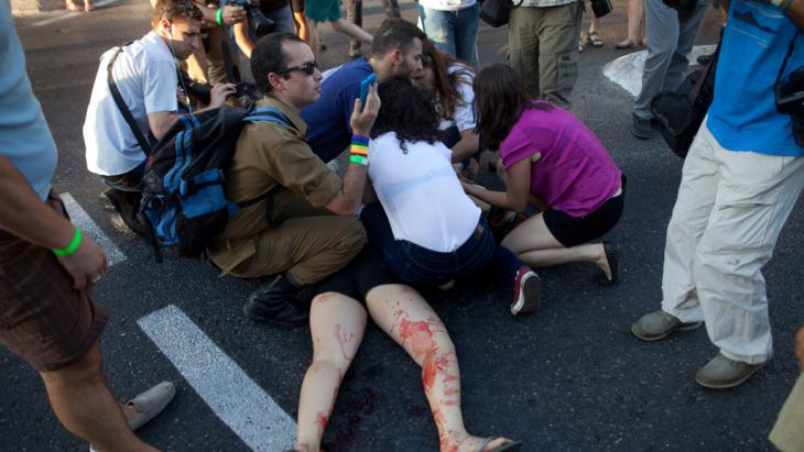 People rush to the aid of the victim of a knife attack on the Gay Pride Parade in Jerusalem, 30 July 2015 (photo: Getty Images/L. Mizrahi)