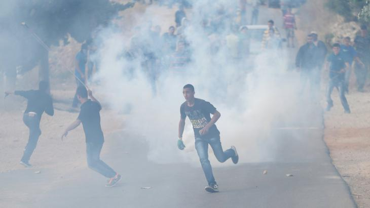 A Palestinian protester runs from tear gas fired by Israeli troops during a protest against the Jewish settlement of Ofra, in the West Bank village of Silwad, near Ramallah, 5 June 2015 (photo: Reuters/Mohamad Torokman)