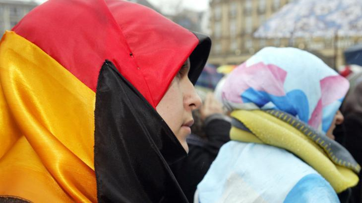 "A woman wears a German flag as a headscarf at a demonstration against the ban on headscarves and ""pseudo press freedom"" in Germany (photo: picture-alliance/dpa)"