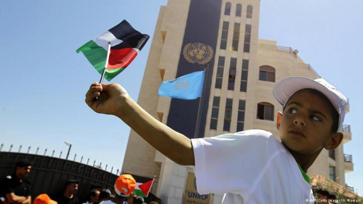 A Palestinian boy waves the national flag in front of the UN office in Ramallah (photo: AFP/Getty Images)