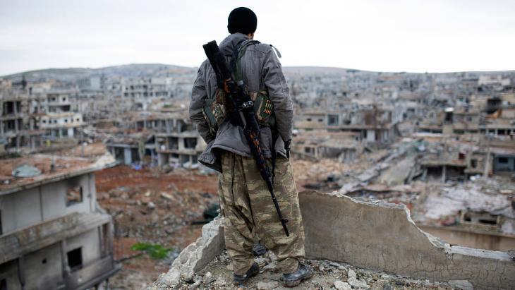 A Krudish sniper surveys the devastation of Kobani (photo: picture alliance/AP)