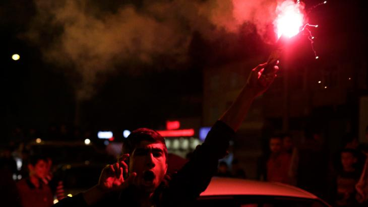 A man burns a flare outside the headquarters of Turkey's pro-Kurdish HDP opposition party in Diyarbakir on 1 November 2015 (photo: Reuters/S. Nenov)
