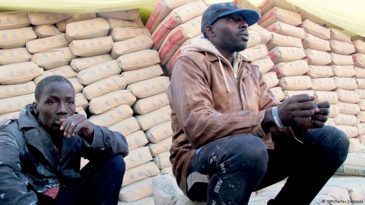 Men crouch on a street in Zuwara, waiting for occasional work