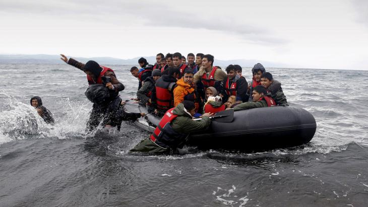 Refugees in a rubber dinghy land at Lesbos (photo : Reuters/Y. Behrakis)