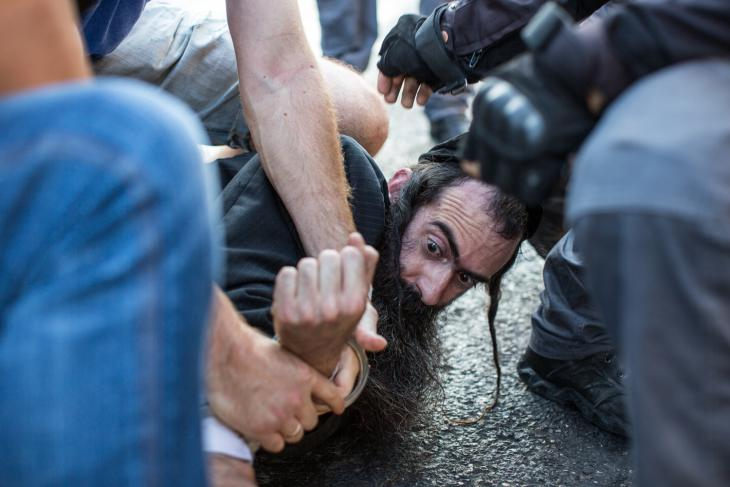 Knife-wielding assailant is wrestled to the ground at Jerusalem's Gay Pride Parade (photo: Emil Salman/ Haaretz)