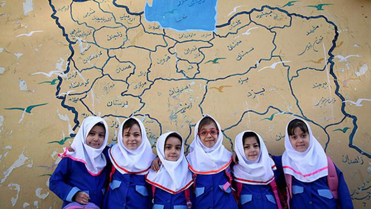 Iranian schoolgirls pose in front of a map of Iran (photo: MEHR)
