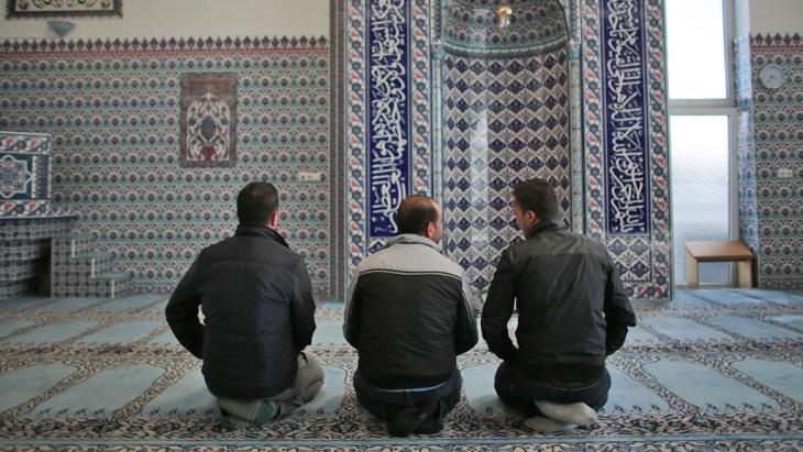 Syrian refugees Sharif Baraa, Jarkas Anas, Mohammad Amin (r-l) praying in the Ditib Mosque in Cologne Chorweiler on 15.09.2015 (photo: picture-alliance)