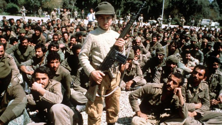 Young Iranian boy poses with a machine gun in front of Iraqi POWs in Suze-Desfoul, April 1982 (photo: picture-alliance/image archive)