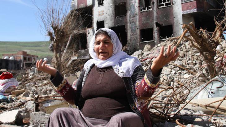 Eine Frau in den Trümern ihres zerstörten Hauses; Foto: DW