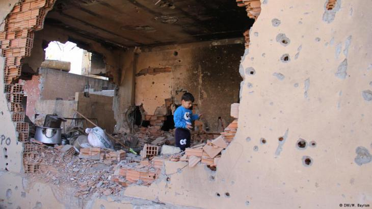 A Kurdish child in a house destroyed by the fighting (photo: DW)