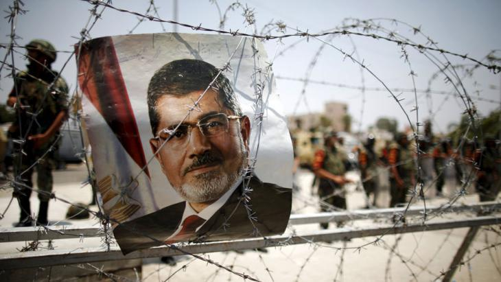 Mohammed Morsi poster caught in barbed wire (photo: picture-alliance/dpa/K. Elfiq)