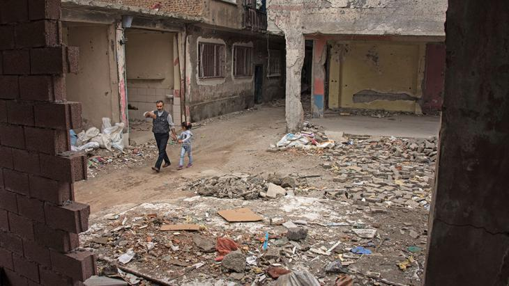 A man and child walk between rubble in the Sur neighbourhood of Diyarbakir (photo: DW)