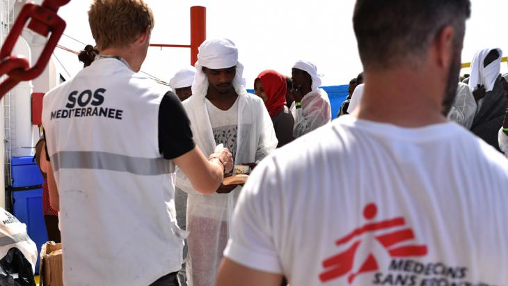 Medecins Sans Frontieres and SOS Mediteranee workers distribute food among refugees aboard the rescue ship Aquarius off the Libyan coast, 25.05.2016 (photo: GABRIEL BOUYS/AFP/Getty Images)