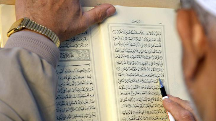 Man reads the Koran; photo: dpa/ picture-alliance