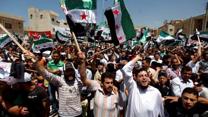 Syrians attend an anti-Assad demon following Friday prayers in the rebel stronghold of Idlib (photo: AP)