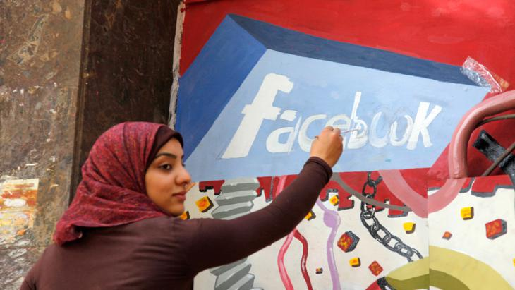 Art student from Helwan University paints a Facebook logo on a mural commemorating the toppling of Hosni Mubarak in Egypt (photo: picture-alliance/AP/M. Deghati)