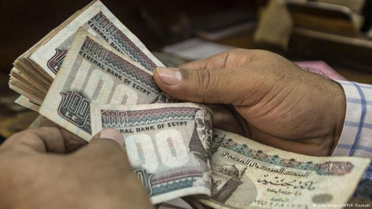 Counting out Egyptian pounds in a Cairo shop