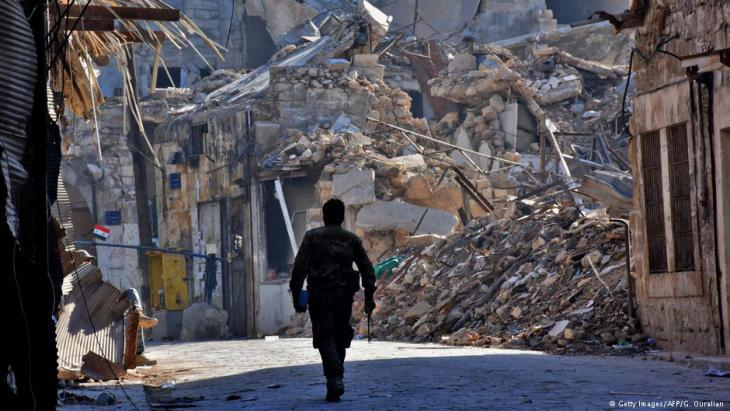 Pro-Assad fighter in the rubble of Aleppo (photo: AFP/Getty Images)