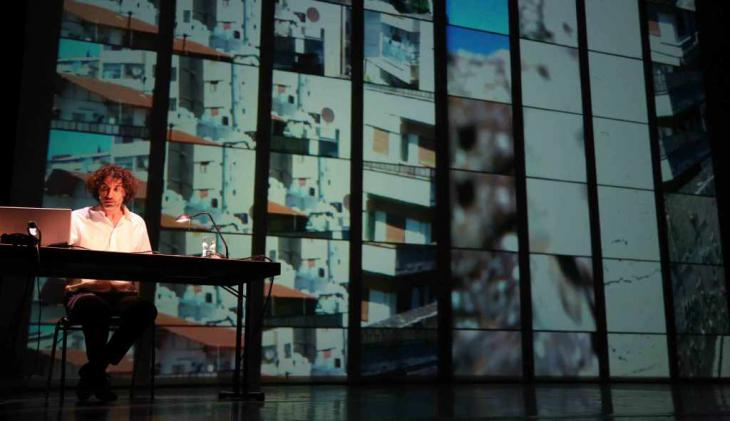 """Rabih Mroué sits in front of a projection during his lecture performance """"The Pixelated Revolution"""" (source: Kampnagel.de)"""