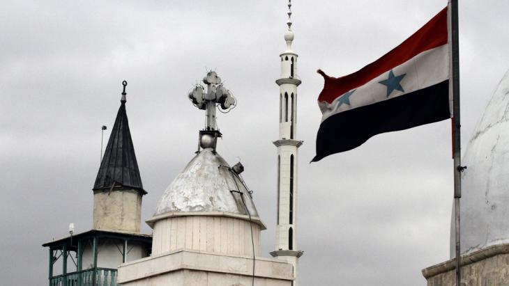A Syrian flag flies alongside the Saint Sarkis Church in Damascus (photo: Getty Images/LOUAI BESHARA)