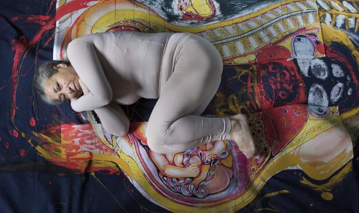 An elderly participant in the photo project lies in the foetal position on a painted background (photo: Heba Khalifa)
