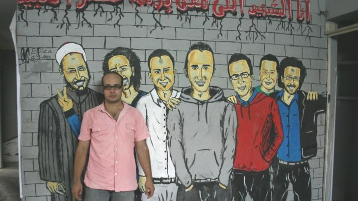 Ahmed Maher stands in front of revolution graffiti in Cairo (photo: Markus Symank)
