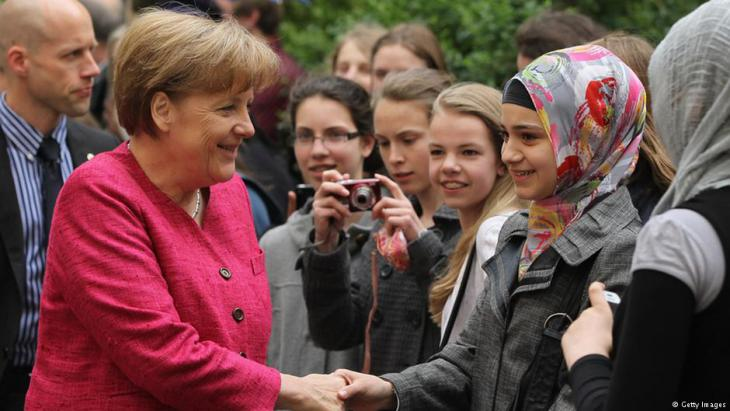 German Chancellor Angela Merkel greets students at the Sophie Scholl senior school in Berlin during a visit on the fifth European School Project Day in 2011