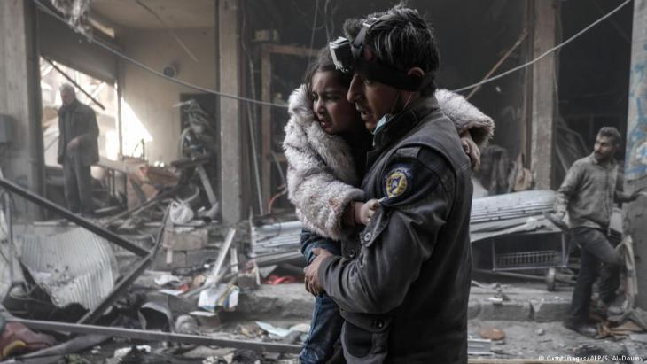 Wounded girl being carried from the rubble by a member of the White Helmets in the rebel-held town of Douma, Syria, in February 2017 (photo: Sameer Al-Doumy/AFP/Getty Images)